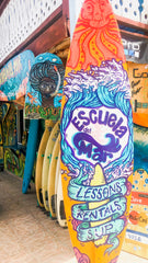 An orange surfboard with purple hand lettering in Spanish