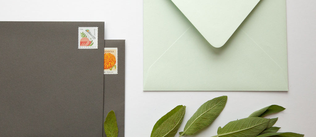 A mint green envelope next to two grey envelopes with colorful stamps