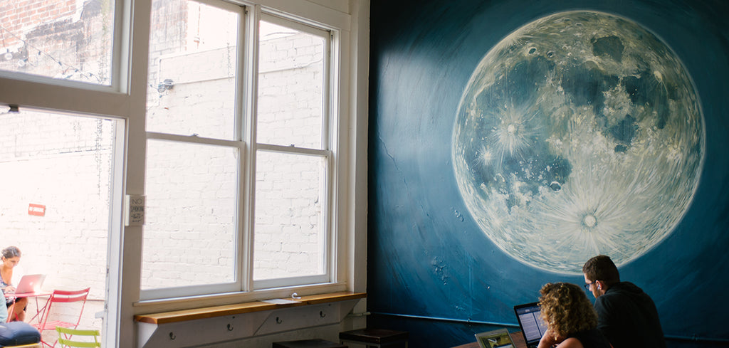 the moon mural next to the communal tables