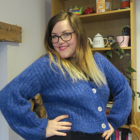 Hannah, a mid-size female with long brown hair fading to blonde ends, wears a fluffy blue cardigan and poses with her hands on her hips.