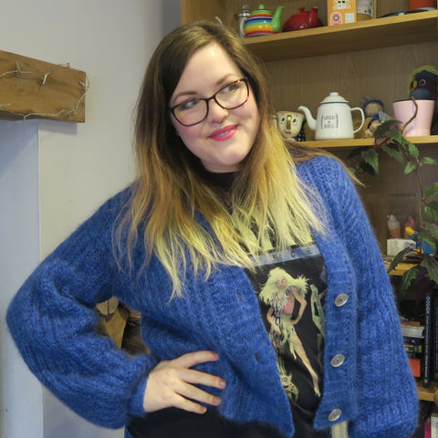Hannah, a mid-size lady with long hair going from brown roots to blonde ends, wearing a vibrant blue, fluffy cardigan unbuttoned, with a hand on her hip.