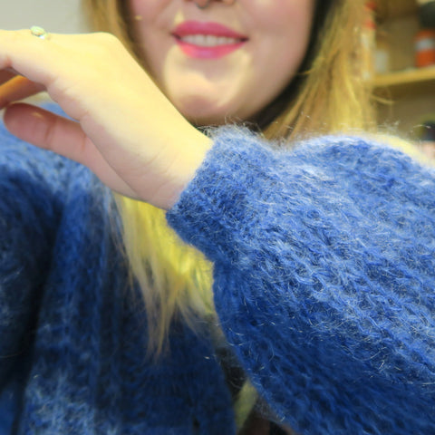 A white hand is in front of the camera, showing off a poofy sleeve with a tighter cuff, knit out of a fluffy, bright blue yarn.