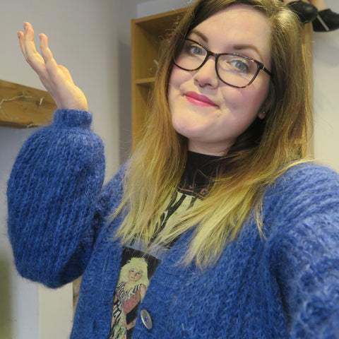 Hannah, a mid-size, white female, poses with a smile on her face and a hand in the air, wearing a vibrant blue, fluffy cardigan.