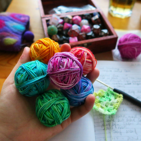 Brightly coloured mini skeins balled up, with a box of dice in the background