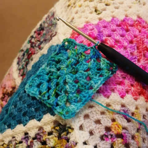 Turquoise granny square with colourful crochet blanket behind