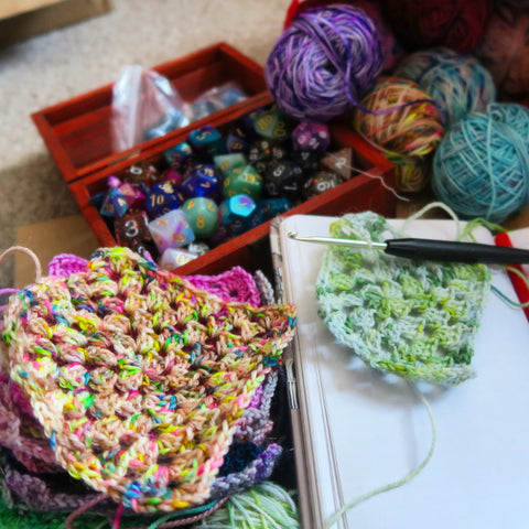 A box of dice sits behind a stack of colourful, crocheted granny squares.
