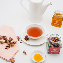 Load image into Gallery viewer, Tea with hibiscus, cacao beans, orange peel, elder berry, aronia berry, star anise, goji berry, rosa damascena, cinnamon, stevia leaf and a flask of honey.