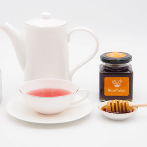 A flask with Pink Label tea, a cup of tea and a flask of honey.