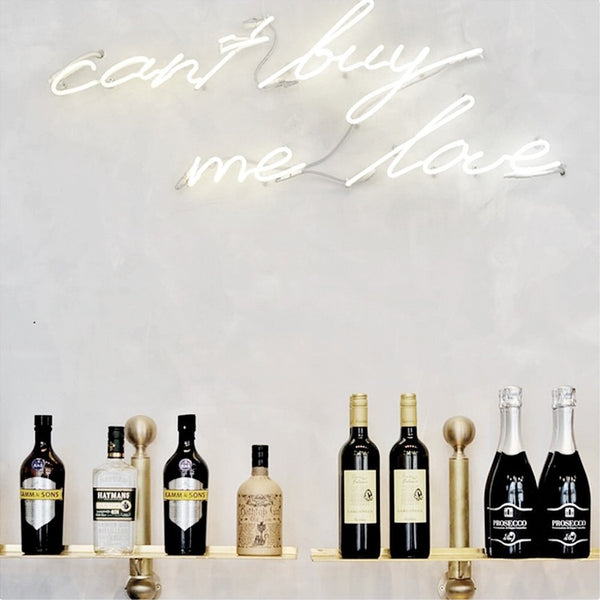 Can't buy me love neon against grey concrete wall with alcohol bottles and gold finishes