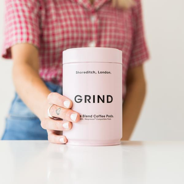 woman holding Grind pink tin on table