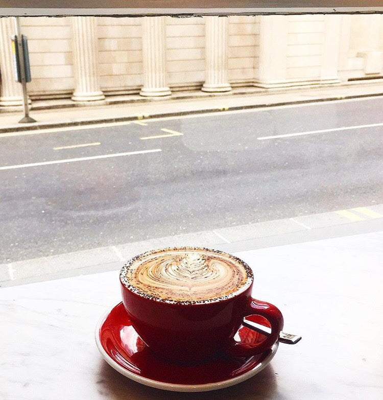 Grind cappuccino in red cup looking out to the street