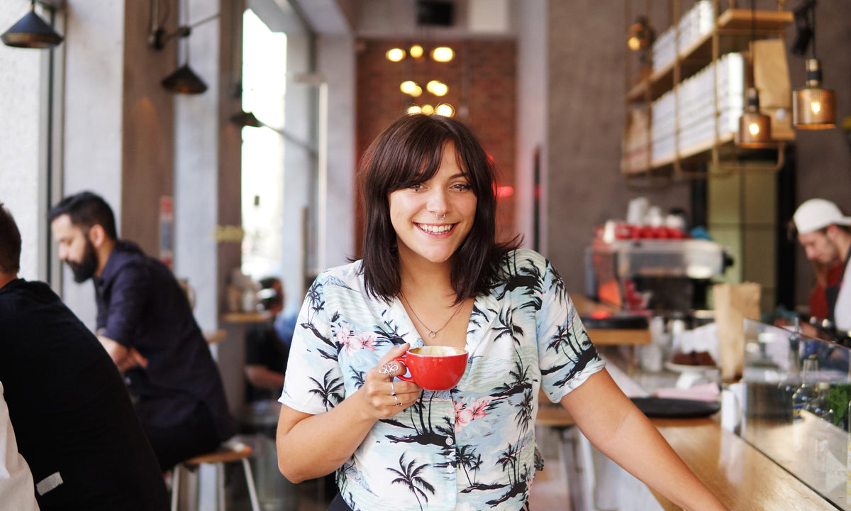 Girl smiling at camera holding coffee in a coffee shop