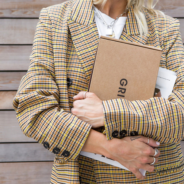 Woman in blazer holding a box of refill packs