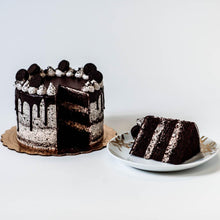 Load image into Gallery viewer, Cocoa and Fig Cookies & Cream Cake Sliced