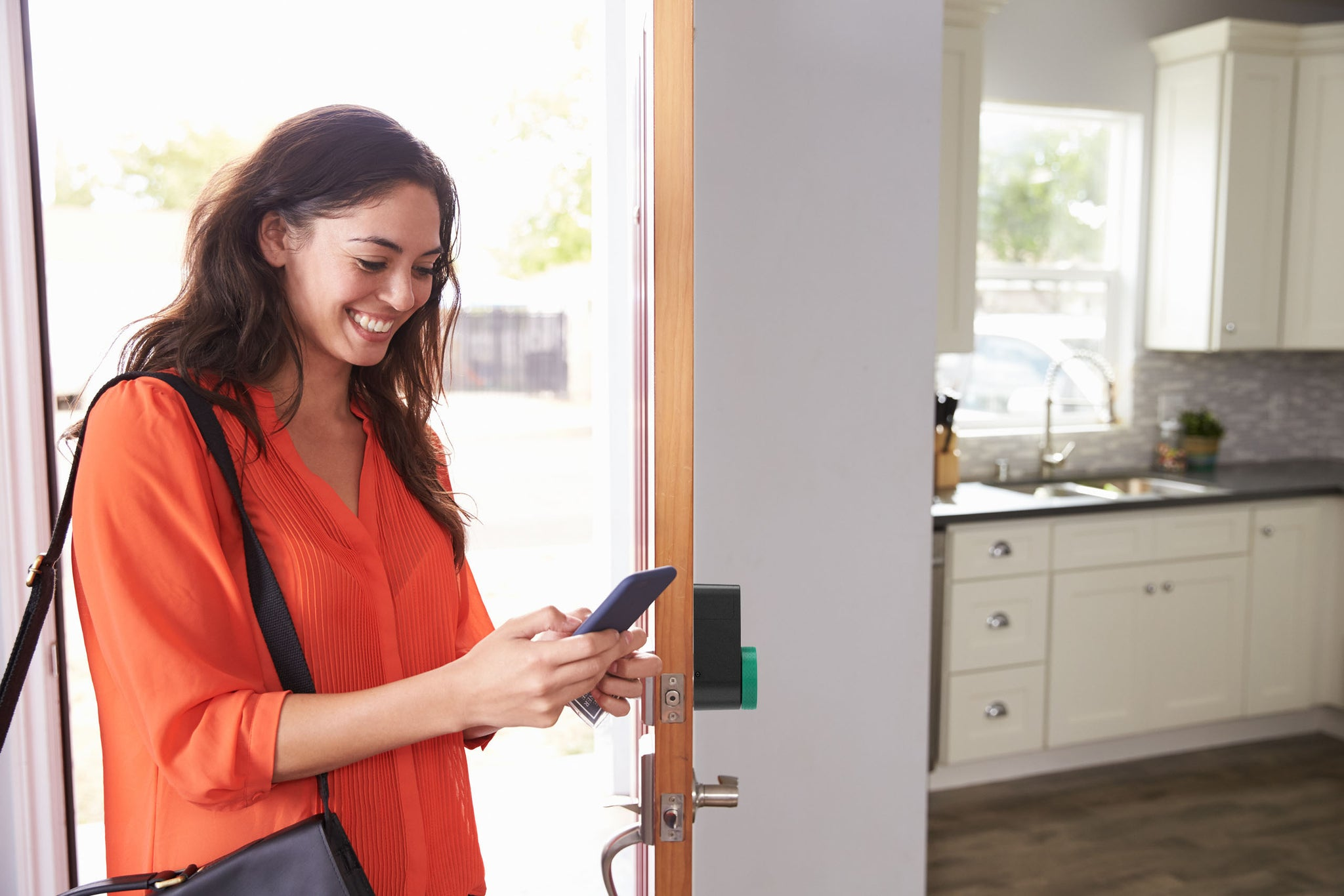 Girl entering the house using the smartphone and smart lock