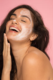 Woman applying Vasanti 4-Step Skincare Travel Kit on half of her face