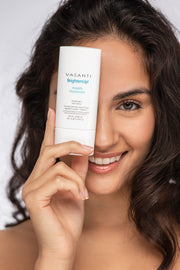 Headshot of a smiling model holding Vasanti Brighten Up! Amplifying Moisturizer infront of her right eye.