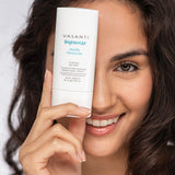 Beauty shot of a model holding Vasanti Brighten Up! Amplifying Moisturizer infront of her right eye