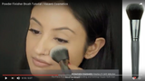 A girl applying powder using Vasanti Powder Finisher - Finish it off Brush - Screenshot from Youtube video