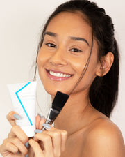 Model holding Vasanti Brighten Up! Miracle Mask and Vasanti Brush