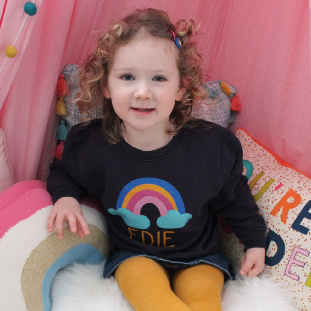 Personalised toddler clothes and gifts by Ruby and the Rainbow. Model wears personalised rainbow toddler jumper. It makes the perfect personalised toddler gift.