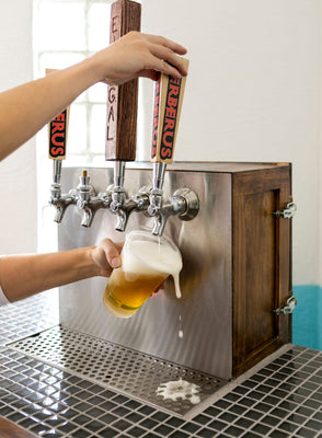 Bartender pouring a brew from a tap