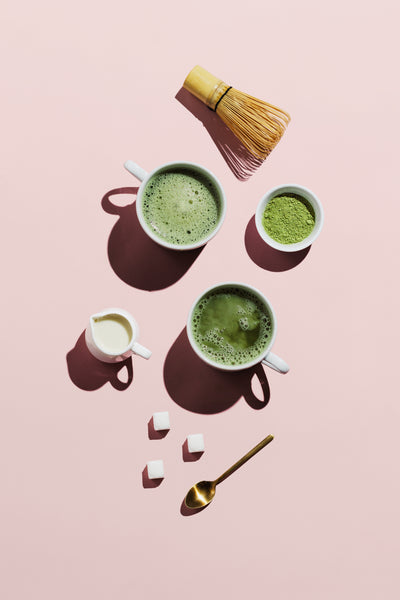 Overhead photo of two cups of matcha tea lattes with cream, sugar cubes, spoon and bamboo tea whisk on a pink background.