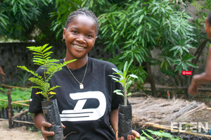 Young girl holding two trees and Eden Reforestation projects logo