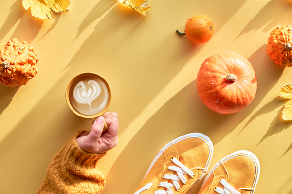 Overhead photo of woman holding a pumpkin spice latte with orange shoes, fall leaves and pumpkins in the background.
