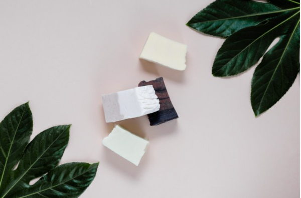 Bar soap on a white background with green leaves around it