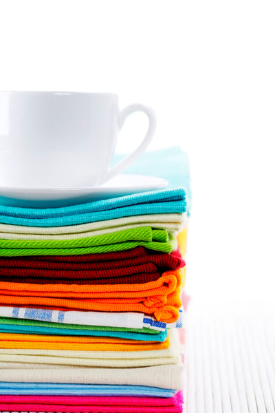 stack of colorful kitchen towels and napkins underneath a white tea cup and saucer on a white background