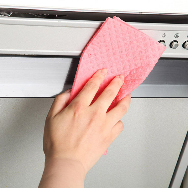 A woman's hand wiping an oven door with a pink Swedish dishcloth to clean it.