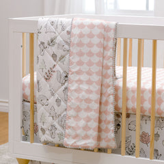 Lolli Living Quilted baby blankets draped over a crib