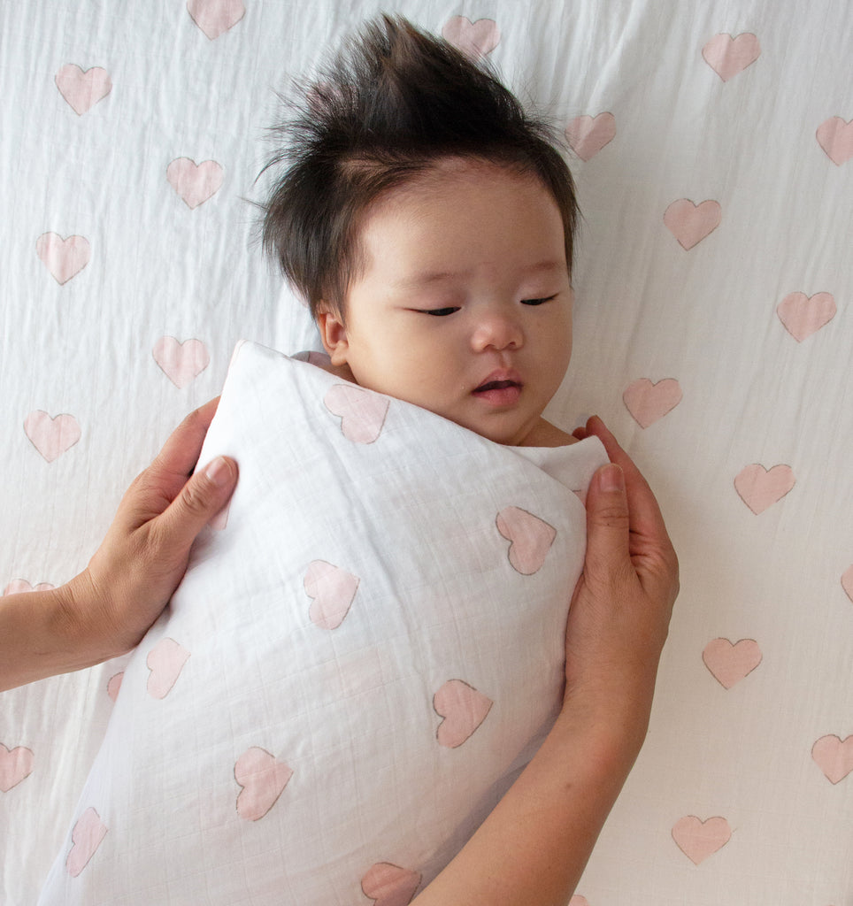 Baby swaddled in pink hearts percale muslin wrap