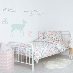 Lolli Living blankets covering a baby bed in a white nursery with animal prints on wall