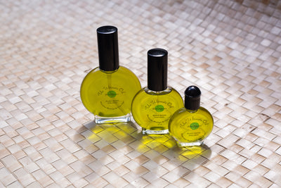 3 different size round clear glass bottles filled with green moringa oil.  labelled with Oahu Organics Ultimate oil and logo