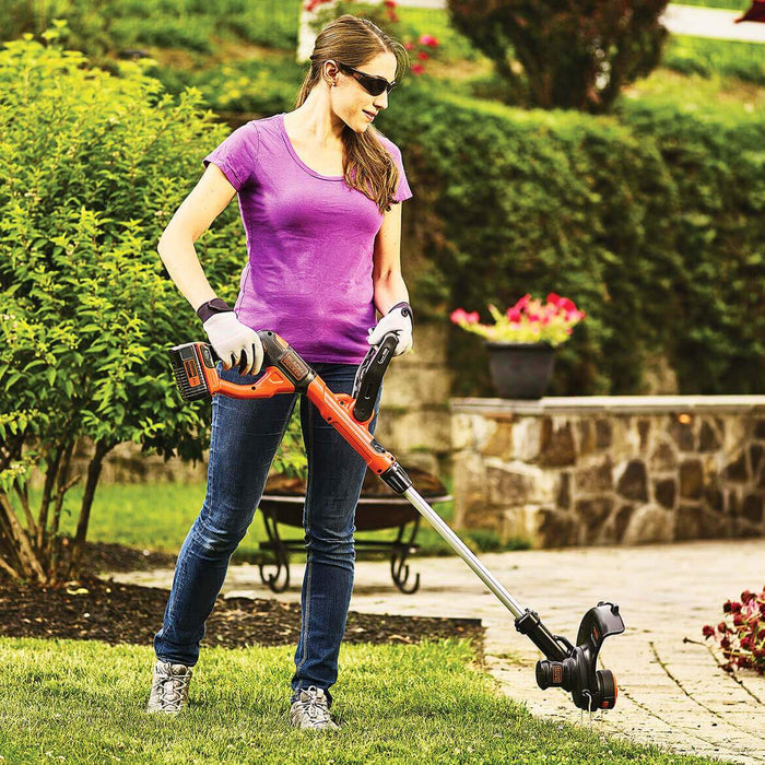woman using the Black and Decker LST140C String Trimmer near the patio
