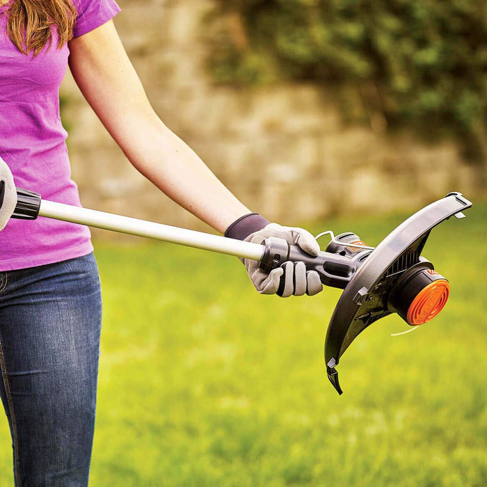 woman retracting the Black and Decker LST140C String Trimmer