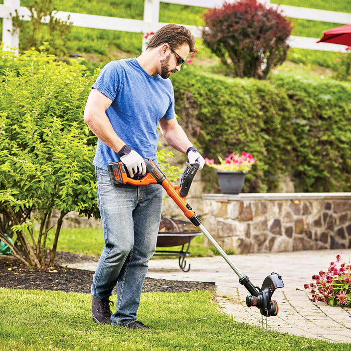 man using the Black and Decker LST140C String Trimmer in the backyard