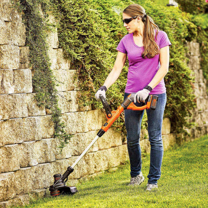 woman using the Black and Decker LST140C String Trimmer in the back yard