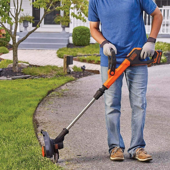Black and Decker LST522 String Trimmer being used in the side walk