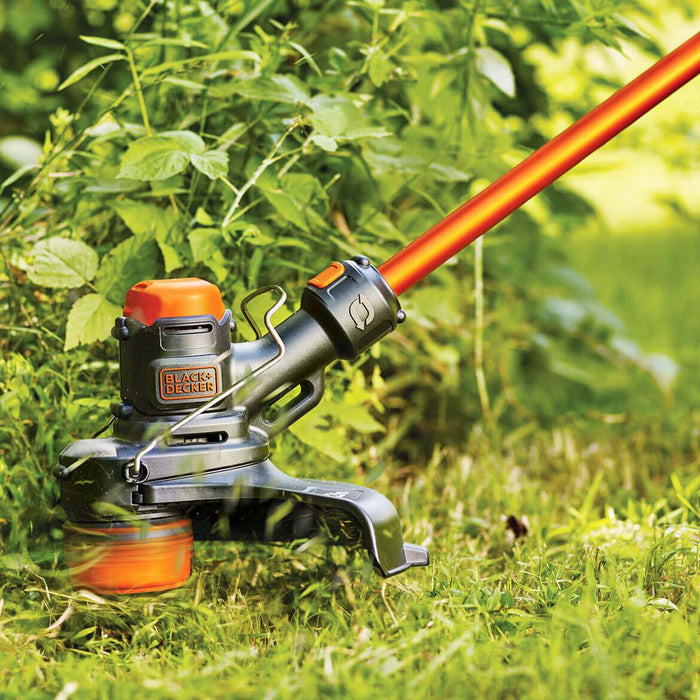 the Black and Decker LST560C String Trimmer being used on a bush