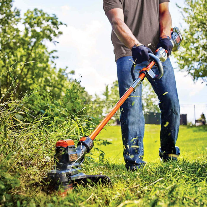 man using Black and Decker LST560C String Trimmer on a bush
