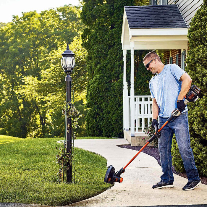 man using Black and Decker LST560C String Trimmer on the side walk