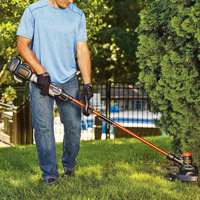man using Black and Decker LST560C String Trimmer on a bush in the patio