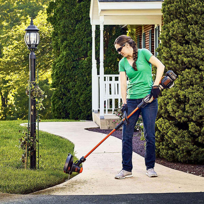 woman using the Black and Decker LST560C String Trimmer as an edger