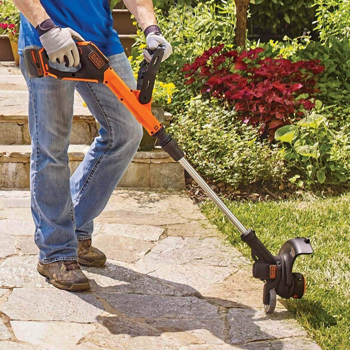 person using the Black and Decker LSTE523 String Trimmer on the yard