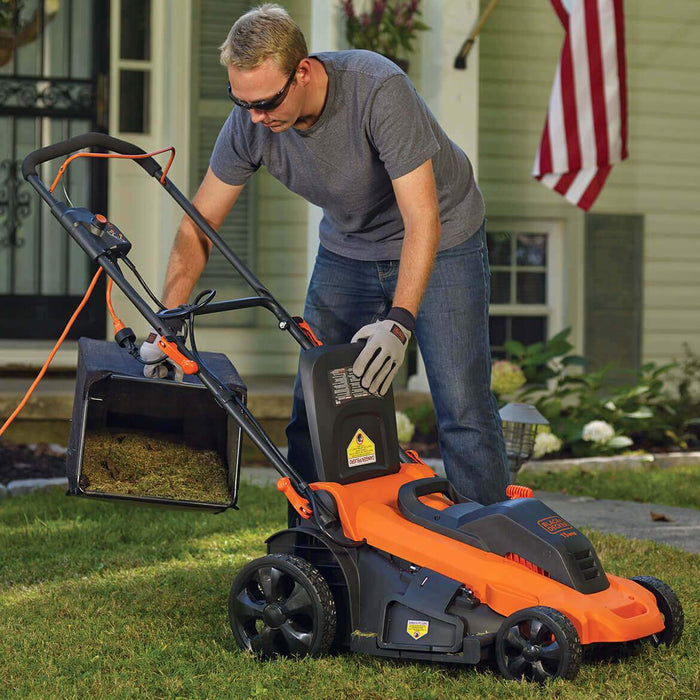 man cleaning out the grass catcher of the Black and Decker MM2000 Electric Lawn Mower