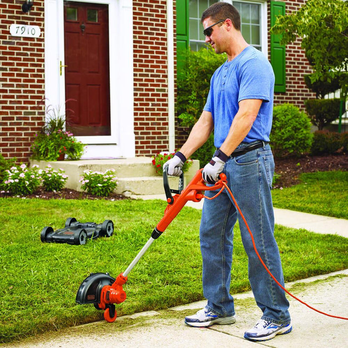 man using the Black and Decker MTE912 Trimmer Edger Mower as an edger on the front lawn