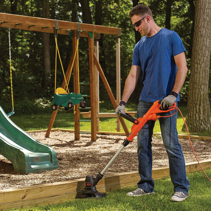 man using the Black and Decker ST8600 String Trimmer at a playground